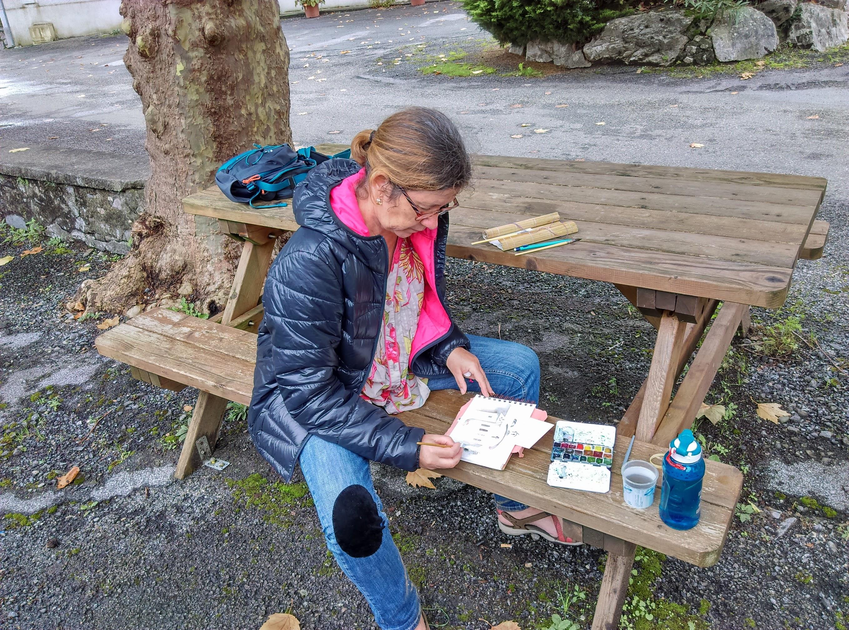Photographie, Cécile est assise à cheval sur le banc d'une table de pique-nique en bois. Elle peind. Le carnet de peinture est devant elle, puis le petite palette, puis le godet d'eau et le gourde. Elle tient un pinceau à main droite.
